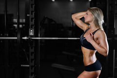 Beautiful fitness woman trains in the gym. Fitness strength training workout bodybuilding concept background - muscular bodybuilder sexy woman doing exercises in Royalty Free Stock Images