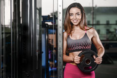 Beautiful fitness woman trains in the gym Stock Image