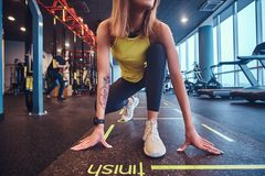Beautiful fitness woman wearing sportswear standing in start position, ready for run, in the modern gym. Beautiful fitness women wearing sportswear standing in royalty free stock photos