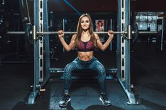 Beautiful fitness young girls doing squats with the barbell in smith machine at the gym. Perfect fitness female figure royalty free stock photography