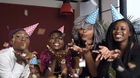 Beautiful five african girl blowing golden confetti during birthday party. Beautiful five african girl blowing golden confetti during birthday party in the red stock video