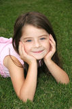 Beautiful Five Year Old. Darling little girl laying in the green grass Royalty Free Stock Photo