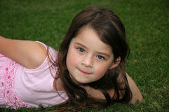 Beautiful Five Year Old Girl. Adorable little girl laying in the grass Stock Images