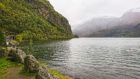 Beautiful fjord in autumn twilight, mountain peaks with first snow, small villages, Norway. stock image