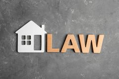 Beautiful flat lay composition with word LAW and house model on grey background. Flat lay composition with word LAW and house model on grey background royalty free stock photography