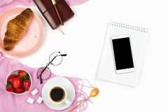 Beautiful flatlay arrangement with croissant, cup of coffee, fresh strawberries, smartphone with black copyspace and other busines. S accessories: concept of royalty free stock photography