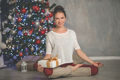 Beautiful flexible smiling woman with gift box is doing stretching exercise near decorated fashion xmas tree at home. Pretty flexible smiling woman is wearing Stock Photography