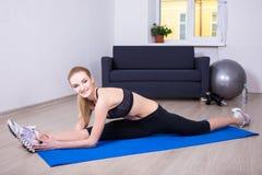 Beautiful flexible woman doing stretching exercise on yoga mat a. Young beautiful flexible woman doing stretching exercise on yoga mat at home Stock Photos