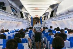 Beautiful flight attendants and passengers. Beautiful flight attendant on board of big plane Royalty Free Stock Images