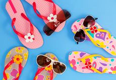 Beautiful flip flops with sunglasses on blue paper background.  stock images