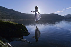 Beautiful Floating Girl dressed in white, silhouetted by the sun reflected in still lake Stock Images