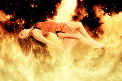 Beautiful Floating woman on fire. Beautiful young woman floating in the air on fire Royalty Free Stock Image