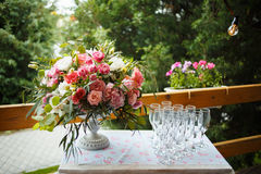 Beautiful floral arrangement of pink and white peonies, roses. Bright bouquet of peony on the wedding table with glasses on a green background Stock Photography