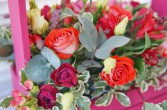 Beautiful floral arrangement of red, pink and burgundy flowers in a pink wooden box stock photo
