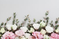 Beautiful floral border of pastel flowers and green eucalyptus leaves on gray table top view. Flat lay composition. Beautiful floral border of pastel flowers and stock images
