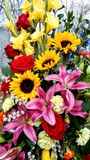 Beautiful Floral Bouquet, Sunflowers, Lillies, Gladiolus, Roses. A beautiful floral arrangement of sunflowers, pink stargazer lillies red roses, yellow gladiolus stock photography