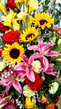 Beautiful Floral Bouquet, Sunflowers, Lillies, Gladiolus, Roses. A beautiful floral arrangement of sunflowers, pink stargazer lillies red roses, yellow gladiolus stock image