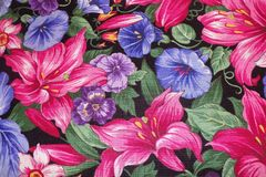 Pink and Purple Flower Fabric for Backgrounds. Beautiful floral fabric in pinks and purples with green leaves for backgrounds royalty free stock images