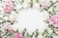 Beautiful floral frame of pastel flowers and eucalyptus leaves on white table top view. Flat lay style. Beautiful floral frame of pastel flowers and eucalyptus royalty free stock image