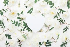 Beautiful floral mockup of pastel rose flowers and green leaves on white table top view. Flat lay greeting card. Royalty Free Stock Photography