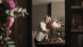 A beautiful florist girl corrects and fills up a bouquet with flowers looking at it in the mirror reflection.  stock video