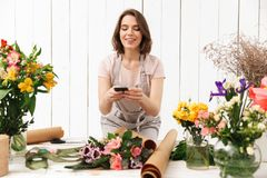 Beautiful florist woman in apron working in flower studio, and t. Beautiful florist woman in apron working in flower studio and taking photo with mobile phone of Royalty Free Stock Images
