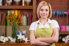 Beautiful florist at working place. Beautiful young female florist keeping arms crossed and looking at camera while standing near her working place stock images