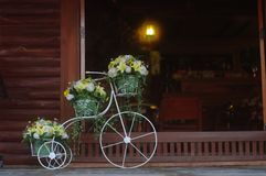The beautiful flower basket on bicycle are parking in front of the door stock photo