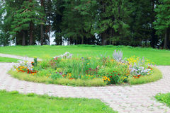 Beautiful flower bed in park with paved paths. And green trees Stock Photo