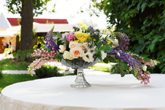 Beautiful flower bouquet outdoors. Wedding floristic decoration at white table Stock Photo
