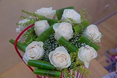 Beautiful flower bouquet of white roses in big round red hat box . Work florist. Mother`s Day. A beautiful round white rose bouquet. A bouquet of red paper Royalty Free Stock Images