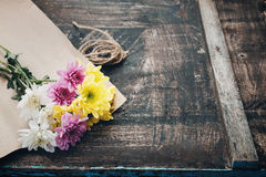 Beautiful flower bouquet wrapped in craft paper on the wooden table background. Royalty Free Stock Image