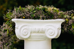 Beautiful flower garland on stone pedestal Royalty Free Stock Photos
