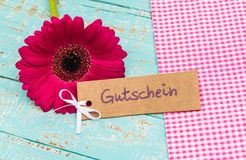Beautiful flower with gift tag with german word, Gutschein, means voucher or coupon for Birthday or Anniversary. Label with german word, Gutschein, means voucher Stock Images
