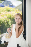Beautiful flower girl with basket near the window. Cute blonde flower girl with basket in white dress Stock Photography