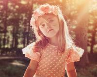Beautiful Flower Girl in Woods with Sunshine. A beautiful little girl is wearing a pink flower crown in the woods with bright sunshine on her face for a peace or royalty free stock images