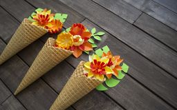 Beautiful flower in ice cream cone on wooden background. Craft paper hobby. Tinker a colorful paper water lily. origami on white isolated background Royalty Free Stock Photo