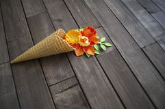Beautiful flower in ice cream cone on wooden background. Craft paper hobby. Tinker a colorful paper water lily. origami on white isolated background Royalty Free Stock Photography