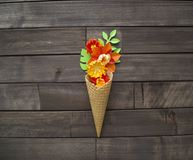 Beautiful flower in ice cream cone on wooden background. Craft paper hobby. Tinker a colorful paper water lily. origami on white isolated background Stock Image