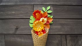 Beautiful flower in ice cream cone on wooden background. Craft paper hobby. Tinker a colorful paper water lily. origami on white isolated background Stock Photography