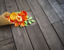 Beautiful flower in ice cream cone on wooden background. Craft paper hobby. stock photo