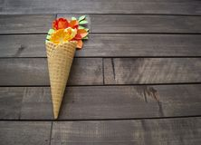 Beautiful flower in ice cream cone on wooden background. Craft paper hobby. Tinker a colorful paper water lily. origami on white isolated background Royalty Free Stock Image