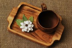 Exclusive clay cup and elegant homemade white flower from pumpkin seeds and bay leaves on beech tray on rough jute canvas. Concept royalty free stock photo