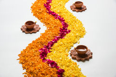 Beautiful Flower rangoli or decoration with clay lamp for diwali or any indian festival. Flower rangoli for Diwali or pongal made using marigold or zendu flowers Stock Image