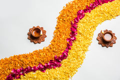 Beautiful Flower rangoli or decoration with clay lamp for diwali or any indian festival. Flower rangoli for Diwali or pongal made using marigold or zendu flowers Royalty Free Stock Photo