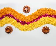 Beautiful Flower rangoli or decoration with clay lamp for diwali or any indian festival. Flower rangoli for Diwali or pongal made using marigold or zendu flowers Royalty Free Stock Image