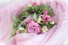 Beautiful flower wreath with colorful blooming flowers on pink veil Stock Photo