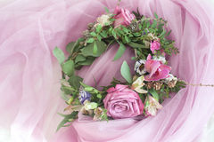 Beautiful flower wreath with colorful blooming flowers on pink veil Stock Photography