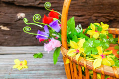 Beautiful flowers in a basket. Beautiful flowers plastic in a basket on brown wooden background Royalty Free Stock Photography