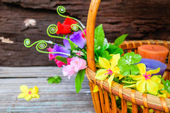 Beautiful flowers in a basket. Beautiful flowers plastic in a basket on brown wooden background Royalty Free Stock Photo